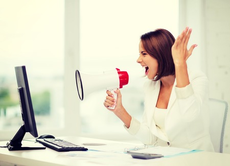 business and technology concept - strict businesswoman shouting in megaphone in office photo