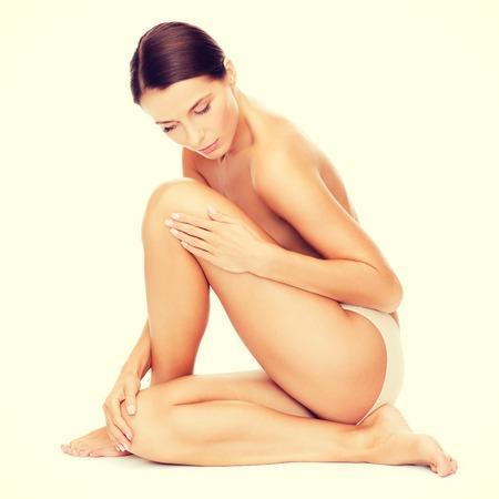 здоровье и красота понятие - красивая голая женщина касаясь ее ногами