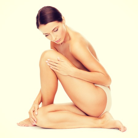 nude woman sitting: health and beauty concept - beautiful naked woman touching her legs