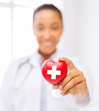 cruz roja: cuidado de la salud y la medicina concepto - femenino africano médico americano celebración de corazón con el símbolo de la cruz roja