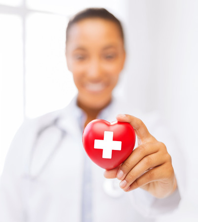 red cross: healthcare and medicine concept - female african american doctor holding heart with red cross symbol