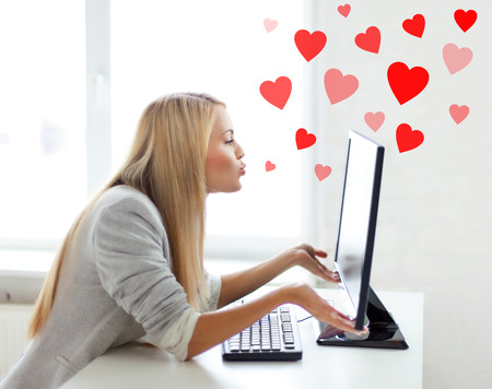 making fun: virtual relationships, online dating and social networking concept - woman sending kisses with computer monitor
