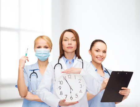 healthcare and medicine concept - calm female doctor and nurses with wall clock and stethoscope photo