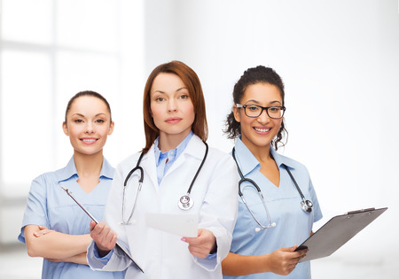 healthcare and medicine concept - calm female doctor and nurses with clipboard and stethoscope giving prescription photo