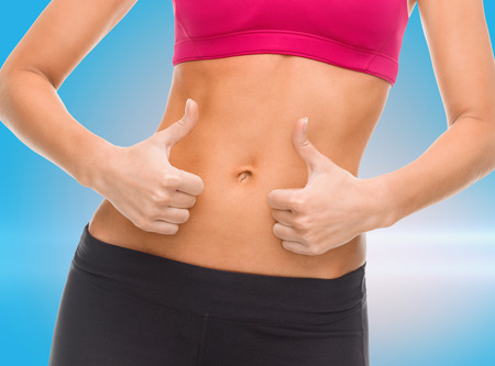 fitness and diet concept - close up of female abs and hands showing thumbs up Banco de Imagens