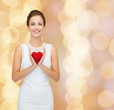 golden heart: happiness, health, charity and love concept - smiling woman in white dress with red heart over golden lights background Stock Photo