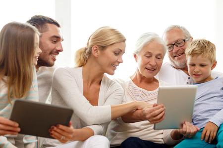 familia, generación, la tecnología y el concepto de la gente - sonriendo familia con computadoras tablet pc en casa