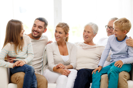 family, happiness, generation and people concept - happy family sitting on couch at home photo