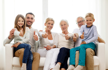 three persons: family, happiness, generation and people concept - happy family sitting on couch and showing thumbs up gesture at home