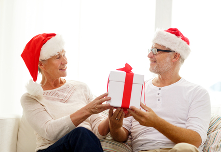 family, holidays, christmas, age and people concept - happy senior couple in santa helper hats with gift box at home photo