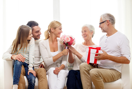 family, happiness, generation, holidays and people concept - happy family with bunch of flowers and gift box sitting on couch at home photo