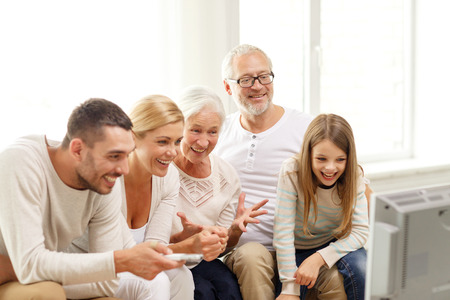 family, happiness, generation and people concept - happy family sitting on sofa and watching tv at home Stock Photo