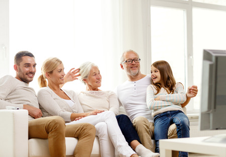 family, happiness, generation and people concept - happy family sitting on sofa and watching tv at home Standard-Bild