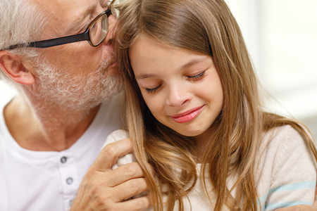 tears: family, support, childhood and people concept - grandfather with crying granddaughter at home