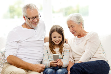 family, generation, technology and people concept - smiling grandfather, granddaughter and grandmother with smartphone sitting on couch at home