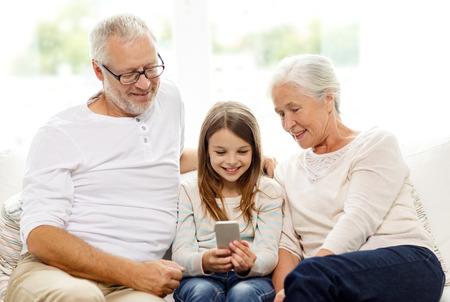 celulas: familia, generaci�n, la tecnolog�a y el concepto de la gente - abuelo sonriente, nieta y abuela con smartphone sentado en el sof� en casa Foto de archivo