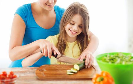 madre e hija adolescente: familia, niño, la cocina y el concepto de casa - una sonrisa de niña con la madre pepino cortar en la cocina