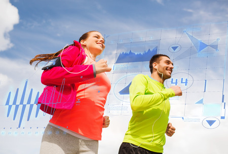 fitness, sport, friendship and lifestyle concept - smiling couple with earphones running outdoors photo