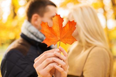 láska, vztah, rodina a lidé koncept - zblízka páru s javorovým listem líbání v podzimním parku