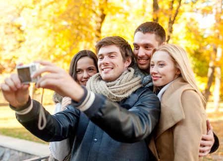 relationship, season, friendship, technology and people concept - group of smiling men and women making self portrait with digital camera in autumn park photo