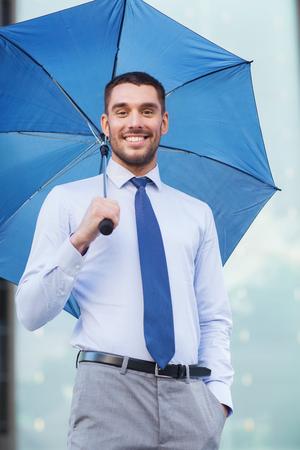 lluvia paraguas: negocio, el mal tiempo y las personas y concepto - hombre de negocios sonriente joven con el paraguas al aire libre