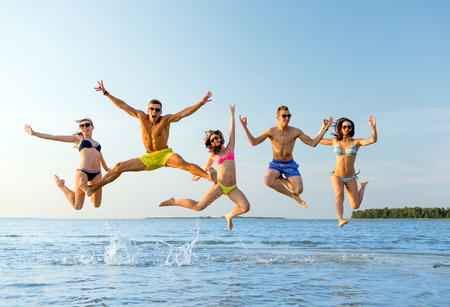 Having Fun: friendship, sea, summer vacation, holidays and people concept - group of smiling friends wearing swimwear and sunglasses talking on beach