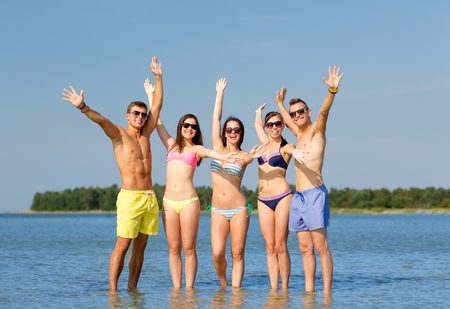friendship, sea, holidays, gesture and people concept - group of smiling friends wearing swimwear and sunglasses waving hands on beach photo