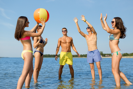 beach ball girl: friendship, sea, summer vacation, holidays and people concept - group of smiling friends wearing swimwear and sunglasses talking on beach