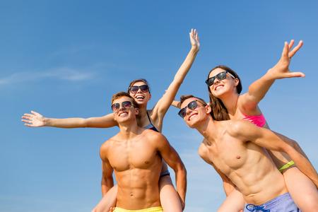 vacaciones en la playa: amistad, mar, vacaciones de verano, vacaciones y concepto de la gente - grupo de amigos sonrientes que llevan el traje de ba�o y gafas de sol que se divierten en la playa Foto de archivo