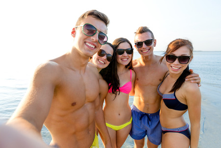 friendship, leisure, summer, technology and people concept - group of smiling friends making selfie on beach photo
