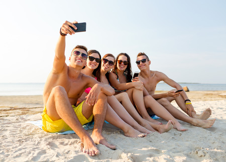self communication: friendship, leisure, summer, technology and people concept - friends sitting and taking selfie with smartphone on beach
