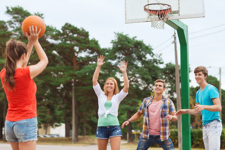 basket ball: summer vacation, holidays, games and friendship concept - group of smiling teenagers playing basketball outdoors