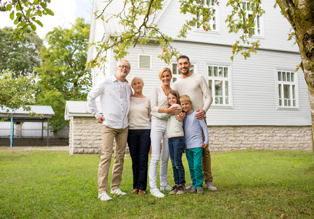 family, happiness, generation, home and people concept - happy family standing in front of house outdoors photo