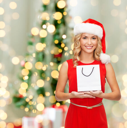 advertisement, holydays and sale concept - smiling woman in santa helper hat with white blank shopping bag over living room with christmas tree background