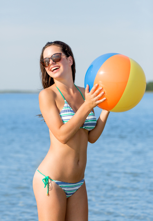 sea, summer vacation, holidays, sport and people concept - smiling teenage girl sunglasses with inflatable ball on beach photo