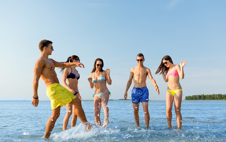 friendship, sea, summer vacation, holidays and people concept - group of happy friends having fun on summer beach photo