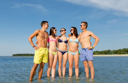 suntanned: friendship, sea, summer vacation, holidays and people concept - group of smiling friends wearing swimwear and sunglasses talking on beach