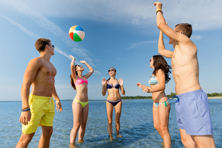 friendship, sea, summer vacation, holidays and people concept - group of smiling friends wearing swimwear and sunglasses talking on beach photo