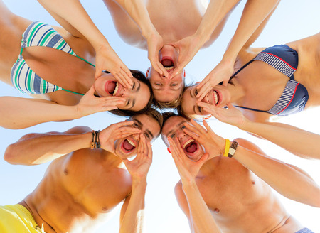 friendship, happiness, summer vacation, holidays and people concept - group of smiling friends wearing swimwear standing in circle and shouting over blue sky Stock Photo