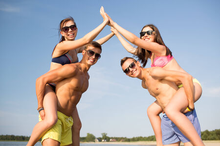 friendship, sea, gesture, holidays and people concept - group of smiling friends wearing swimwear having fun and making high five on beach photo