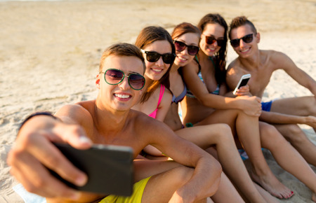 friendship, leisure, summer, technology and people concept - friends sitting and taking selfie with smartphone on beach photo