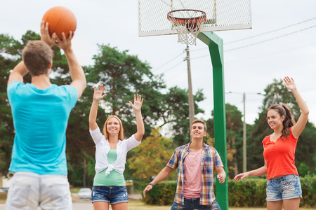 playground basketball: summer vacation, holidays, games and friendship concept - group of smiling teenagers playing basketball outdoors