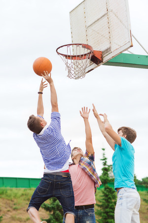 boy basketball: summer vacation, holidays, games and friendship concept - group of teenagers playing basketball outdoors Stock Photo