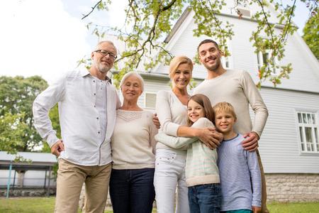 familie, geluk, generatie, thuis en de mensen concept - gelukkige familie die zich in de voorkant van het huis buiten Stockfoto