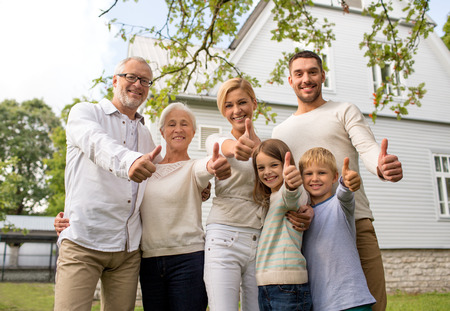 family, happiness, generation, home and people concept - happy family standing in front of house and showing thumbs up outdoors Foto de archivo