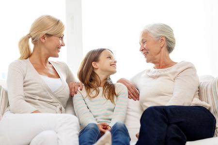 가족, 행복, 세대 및 사람들이 개념 - 어머니, 딸, 할머니 집 소파에 앉아 웃는 스톡 콘텐츠