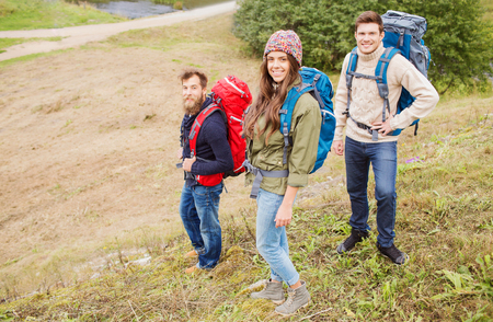 expedition: adventure, travel, tourism, hike and people concept - group of smiling friends with backpacks outdoors