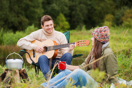 adventure, travel, tourism and people concept - smiling couple with guitar cooking food and drinking in camping photo