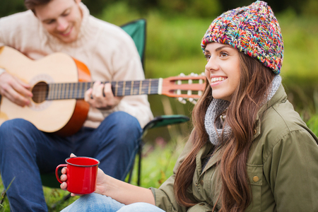 adventure, travel, tourism and people concept - smiling couple with guitar in camping photo