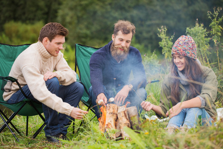campfires: adventure, travel, tourism and people concept - group of smiling friends sitting on chairs around bonfire in camping